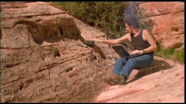 man uses laptops in the desert